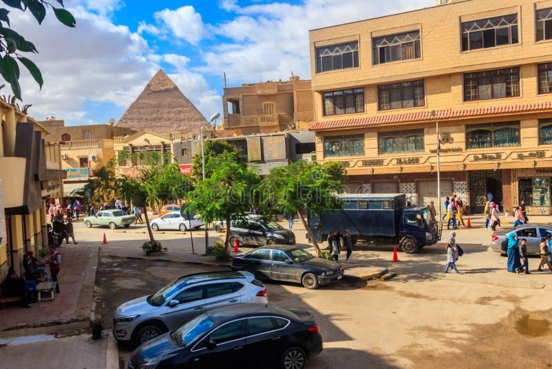 Δρόμος με έντονη κίνηση στο Κάιρο με την κορυφή της πυραμίδας Khafre πίσω από τα σπίτια στοκ φωτογραφία με δικαίωμα ελεύθερης χρήσης