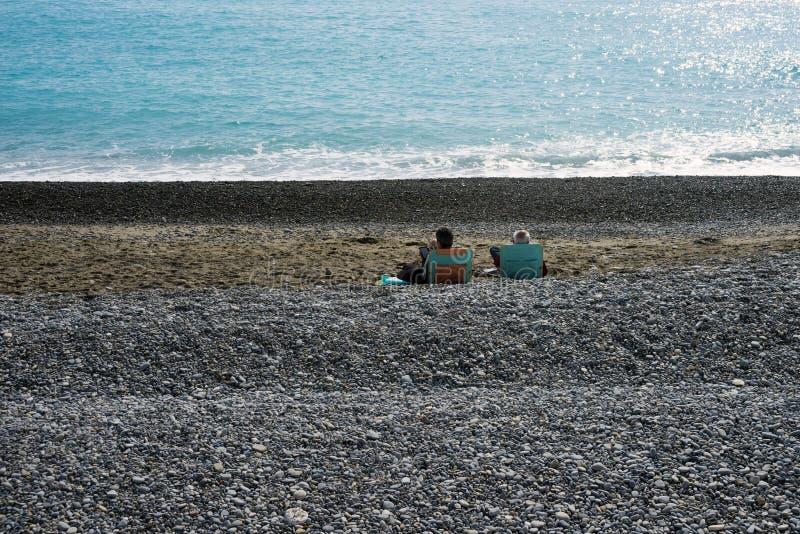 Δύο άνθρωποι που χαλαρώνουν σε μια παραλία χαλικιών από την τυρκουάζ θάλασσα Ανάχωμα της διάσημης γαλλικής πόλης της Νίκαιας στοκ εικόνες