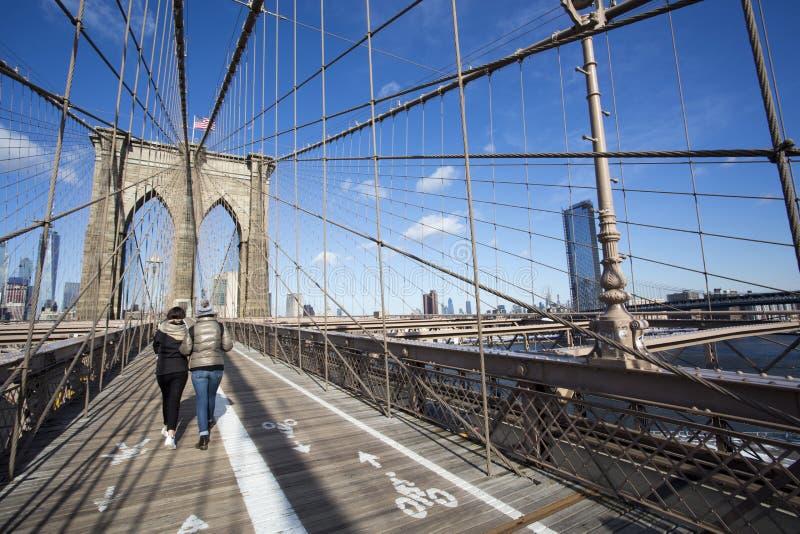 Δύο άνθρωποι που χρησιμοποιούν τη για τους πεζούς διάβαση πεζών γεφυρών του Μπρούκλιν στοκ εικόνες