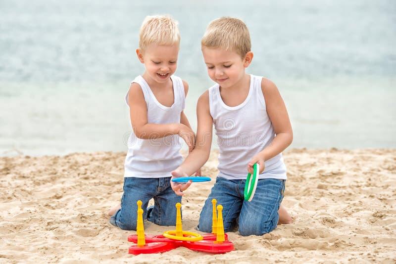 Δύο αδελφοί περπατούν και παίζουν στην παραλία Το παιχνίδι είναι μια εκτίναξη δαχτυλιδιών στοκ εικόνα