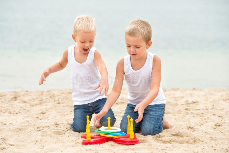 Δύο αδελφοί περπατούν και παίζουν στην παραλία Το παιχνίδι είναι μια εκτίναξη δαχτυλιδιών στοκ εικόνες