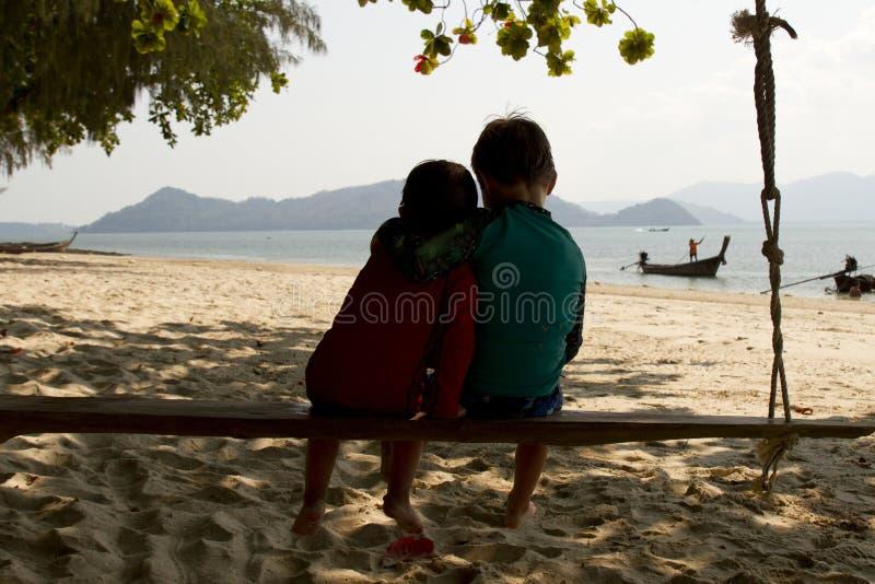 Δύο αδελφοί που κάθονται σε μια ταλάντευση στην Ταϊλάνδη στοκ εικόνες