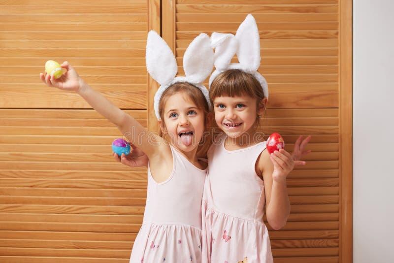 Δύο αστείες γοητευτικές μικρές αδελφές στα φορέματα με τα αυτιά του άσπρου κουνελιού στα κεφάλια τους κρατούν τα βαμμένα αυγά στα στοκ εικόνα με δικαίωμα ελεύθερης χρήσης