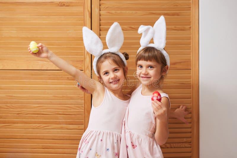 Δύο αστείες γοητευτικές μικρές αδελφές στα φορέματα με τα αυτιά του άσπρου κουνελιού στα κεφάλια τους κρατούν τα βαμμένα αυγά στα στοκ φωτογραφία