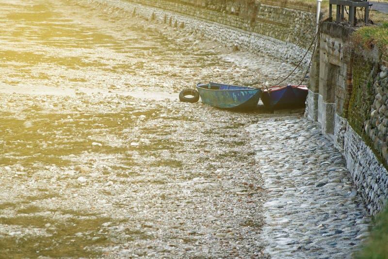Δύο βάρκα, ξηρασία ποταμών, μπλε βάρκα χωρίς οφειλόμενη παγκόσμια αύξηση της θερμοκρασίας λόγω του φαινομένου του θερμοκηπίου νερ στοκ εικόνες