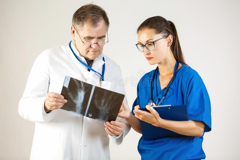 Δύο γιατροί εξετάζουν μια ακτίνα X του χεριού και συζητούν το πρόβλημα στοκ φωτογραφία