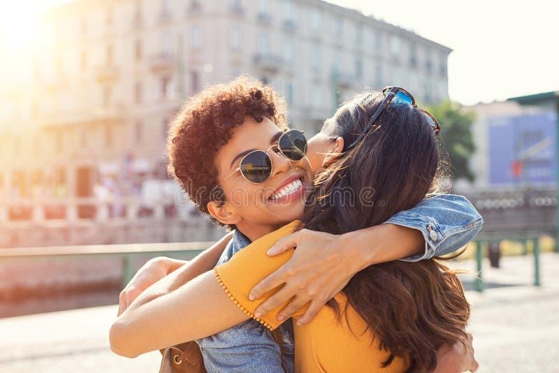 Δύο γυναίκες που αγκαλιάζουν στη πλατεία της πόλης στοκ φωτογραφία