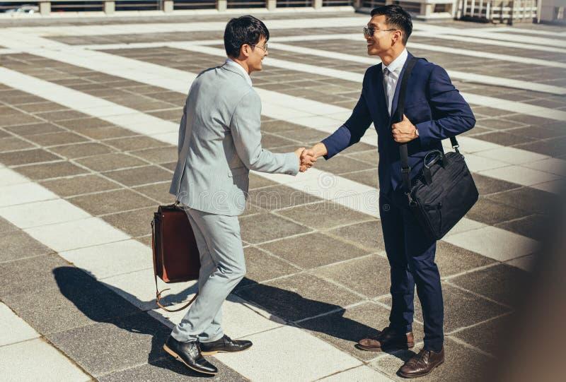 Δύο επιχειρηματίες που τινάζουν τα χέρια υπαίθρια στην πόλη στοκ φωτογραφία