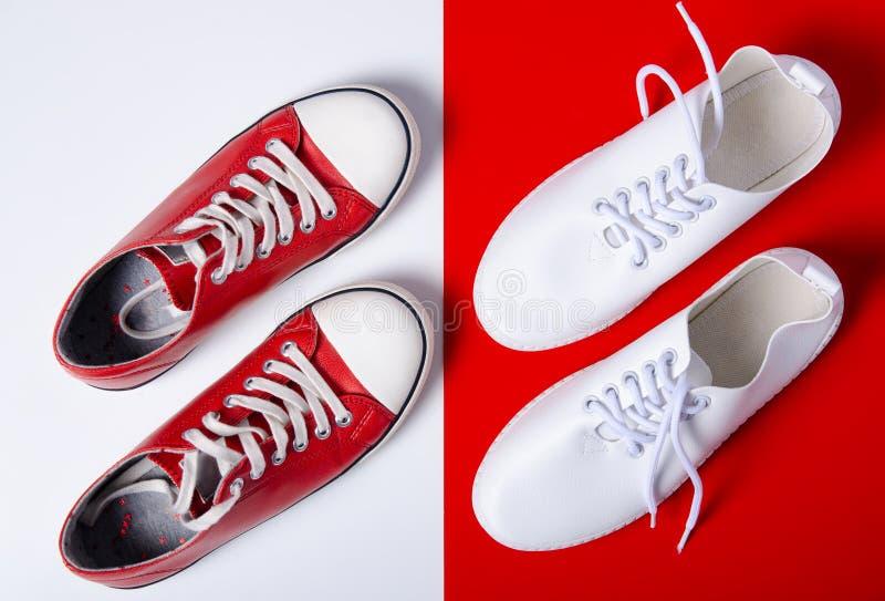 Δύο ζευγάρια των πάνινων παπουτσιών άσπρων και κόκκινων στοκ φωτογραφία