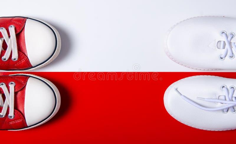 Δύο ζευγάρια των πάνινων παπουτσιών άσπρων και κόκκινων στοκ φωτογραφίες
