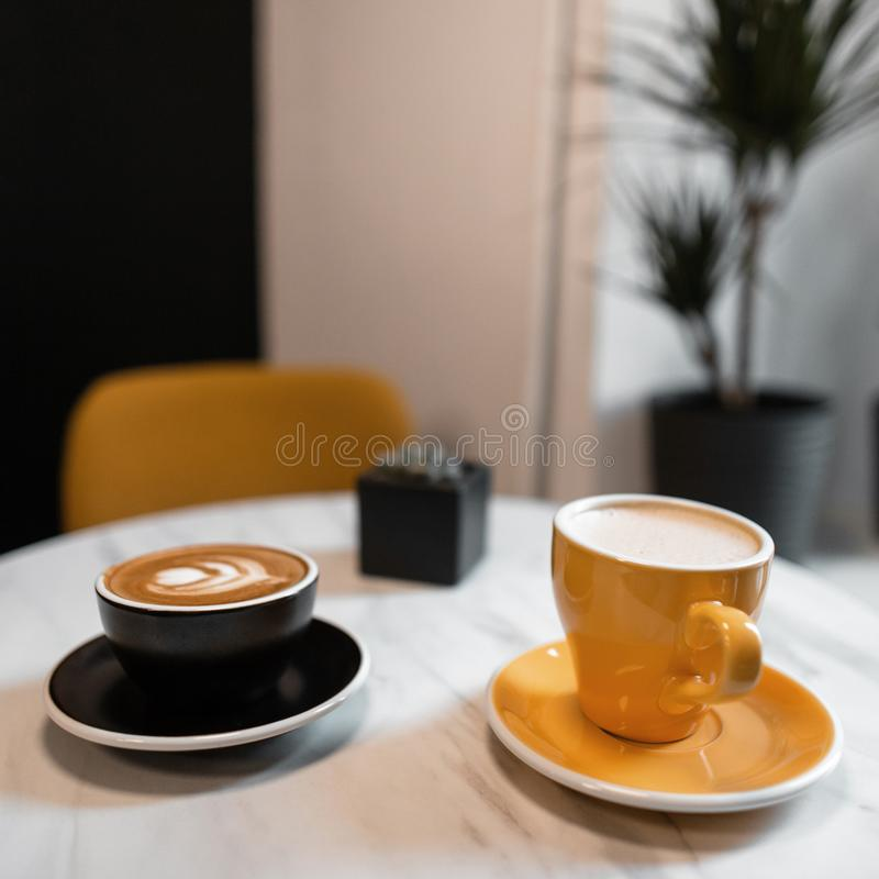 Δύο ζωηρόχρωμα κεραμικά φλυτζάνια καφέ στέκονται σε έναν πίνακα σε έναν εκλεκτής ποιότητας καφέ με ένα εύγευστο cappuccino και έν στοκ φωτογραφία με δικαίωμα ελεύθερης χρήσης