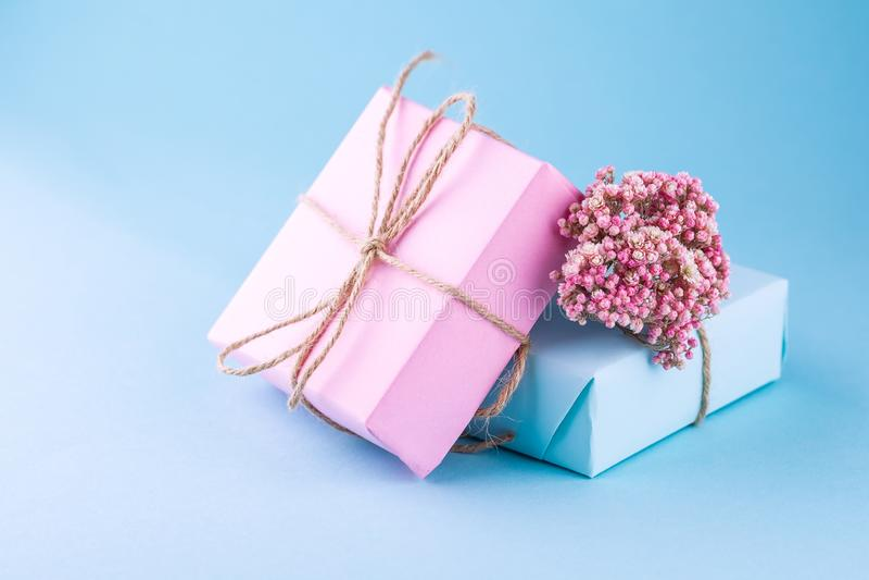 Δύο κιβώτια δώρων του ροζ και του μπλε με τα τόξα του σπάγγου που διακοσμούνται με τα μικρά ρόδινα λουλούδια σε ένα μπλε υπόβαθρο στοκ εικόνα