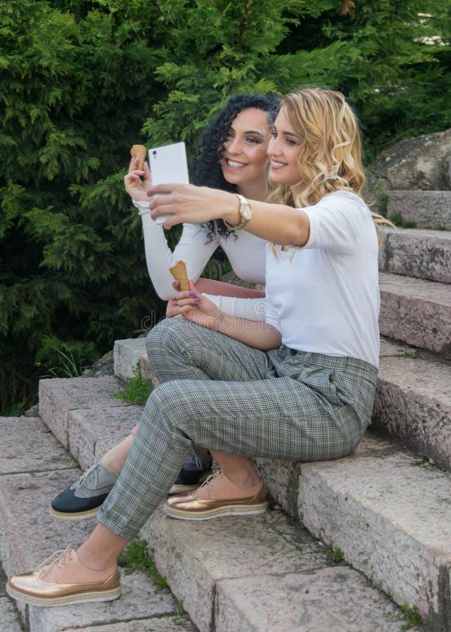 Δύο κορίτσια παίρνουν selfies και τρώνε το παγωτό στοκ εικόνα