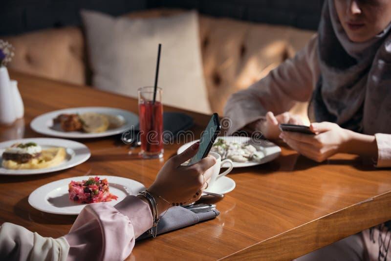 Δύο μουσουλμανικές γυναίκες κάθονται με τις συσκευές σε έναν πίνακα σε ένα εστιατόριο στοκ εικόνα με δικαίωμα ελεύθερης χρήσης