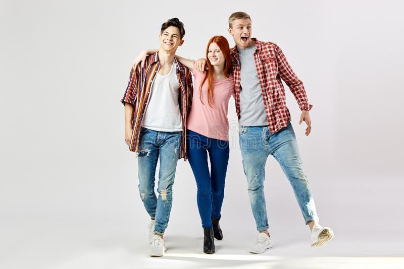 Δύο τύποι και ένα κορίτσι στα μοντέρνα φωτεινά ζωηρόχρωμα ενδύματα περπατούν και χαμόγελο στο άσπρο υπόβαθρο στο στούντιο στοκ εικόνες