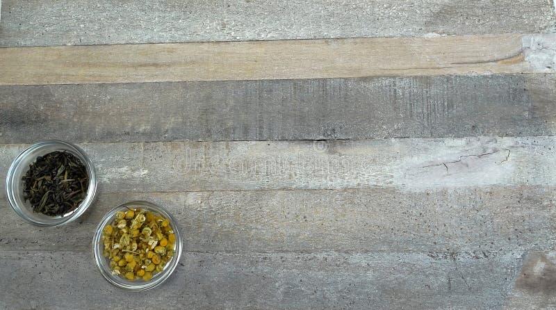 Δύο φλυτζάνια τσαγιού στο γυαλί με το μαύρο τσάι και το chamomile τσάι στο φυσικό ξύλινο υπόβαθρο στοκ φωτογραφία με δικαίωμα ελεύθερης χρήσης