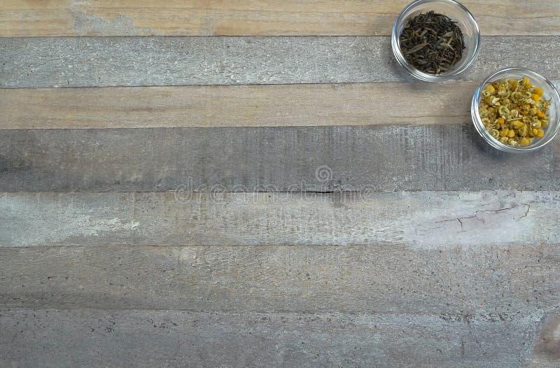 Δύο φλυτζάνια τσαγιού στο γυαλί με το μαύρο τσάι και το chamomile τσάι στο φυσικό ξύλινο υπόβαθρο στοκ φωτογραφία