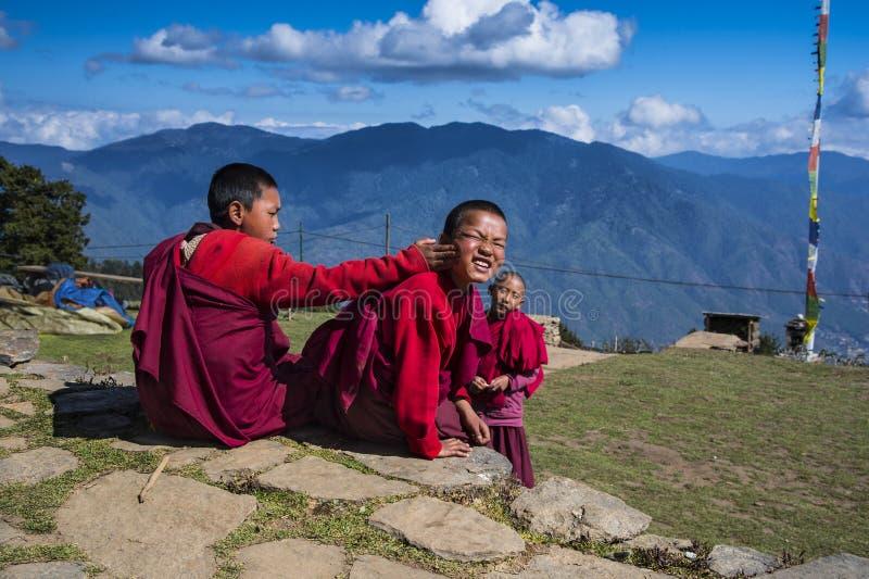 Δύο χαριτωμένοι Bhutanese νέοι μοναχοί αρχαρίων στην κορυφή βουνών, μια γυρίζουν το κεφάλι του και χαμογελούν στοκ εικόνες
