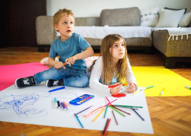 Δύο παιδιά παίζουν και επισύρουν την προσοχή στο πάτωμα στοκ φωτογραφία