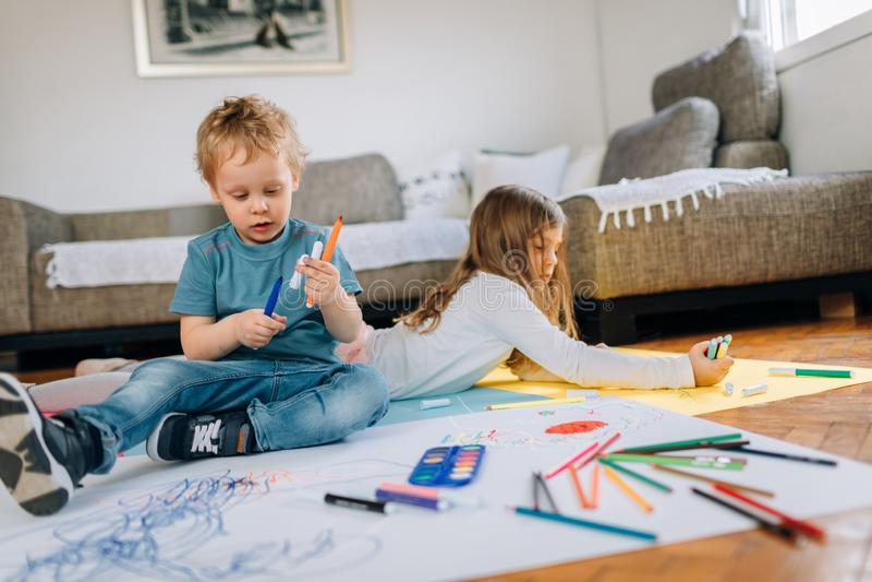 Δύο παιδιά παίζουν και επισύρουν την προσοχή στο πάτωμα στοκ φωτογραφία με δικαίωμα ελεύθερης χρήσης