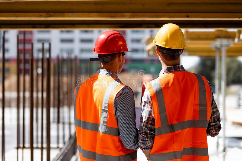 Δύο πολιτικοί μηχανικοί που ντύνονται στις πορτοκαλιά φανέλλες και τα κράνη εργασίας συζητούν τη διαδικασία κατασκευής στο εργοτά στοκ φωτογραφία