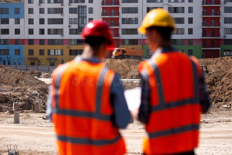 Δύο πολιτικοί μηχανικοί που ντύνονται στις πορτοκαλιά φανέλλες και τα κράνη εργασίας μιλούν για τη διαδικασία κατασκευής στο εργο στοκ εικόνες με δικαίωμα ελεύθερης χρήσης