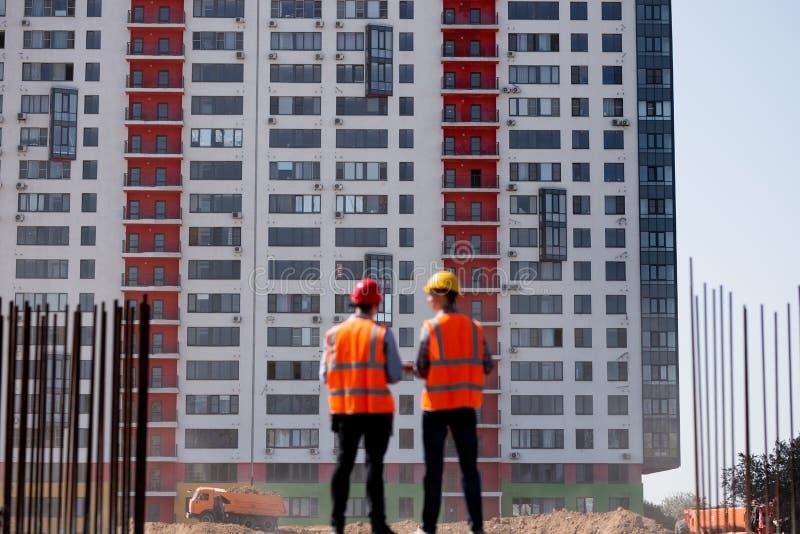 Δύο πολιτικοί μηχανικοί που ντύνονται στις πορτοκαλιά φανέλλες και τα κράνη εργασίας μιλούν για τη διαδικασία κατασκευής στο εργο στοκ εικόνες