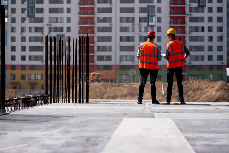 Δύο πολιτικοί μηχανικοί που ντύνονται στις πορτοκαλιά φανέλλες και τα κράνη εργασίας μιλούν για τη διαδικασία κατασκευής στο εργο στοκ φωτογραφίες