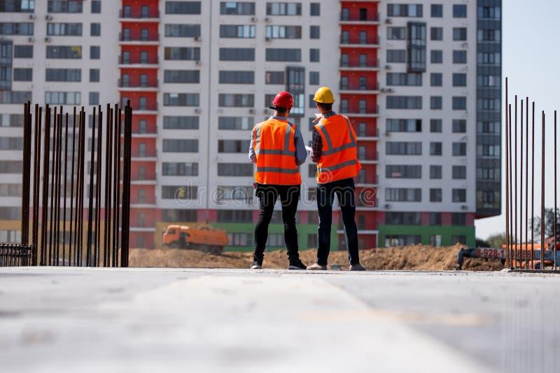 Δύο πολιτικοί μηχανικοί που ντύνονται στις πορτοκαλιά φανέλλες και τα κράνη εργασίας μιλούν για τη διαδικασία κατασκευής στο εργο στοκ εικόνα