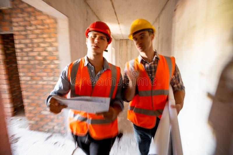Δύο πολιτικοί μηχανικοί που ντύνονται στις πορτοκαλιά φανέλλες και τα κράνη εργασίας περπατούν μέσα στο κτήριο κάτω από την οικοδ στοκ εικόνες