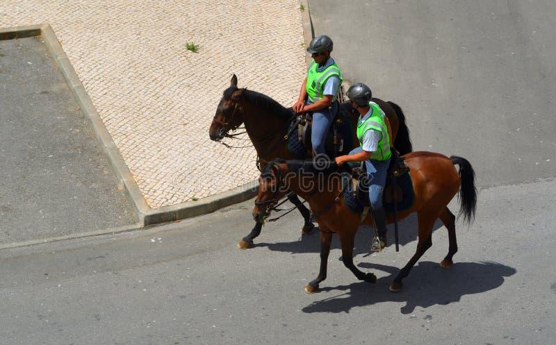 Δύο πορτογαλικοί αστυνομικοί στα άλογα που επιτηρούν τις οδούς στοκ εικόνες