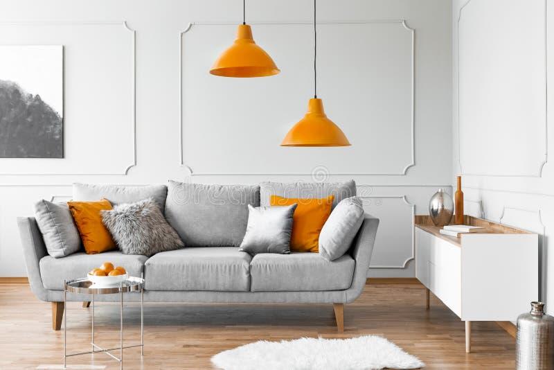 Δύο πορτοκαλιοί λαμπτήρες επάνω από τον γκρίζο Σκανδιναβικό καναπέ με τα μαξιλάρια στοκ εικόνα με δικαίωμα ελεύθερης χρήσης