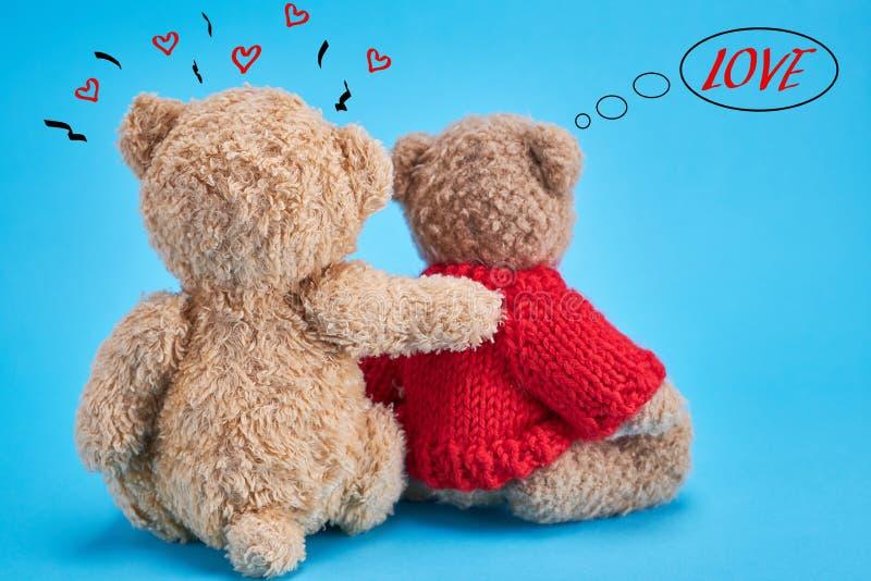 Δύο teddy αρκούδες βελούδου κάθονται πίσω αγκαλιασμένος σε ένα μπλε υπόβαθρο στοκ φωτογραφία με δικαίωμα ελεύθερης χρήσης