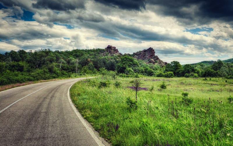 Δύσκολο μέγιστο, δασικό, πράσινο λιβάδι, δρόμος στροφής, δραματικός ουρανός στοκ φωτογραφία