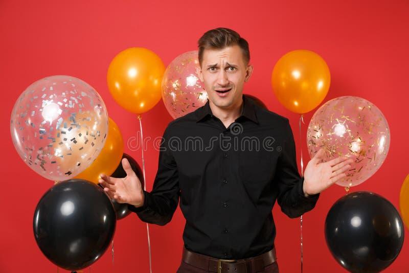 Δύσπιστος μπερδεμένος νεαρός άνδρας στο μαύρο κλασικό εορτασμό πουκάμισων, χέρια διάδοσης στα κόκκινα μπαλόνια αέρα υποβάθρου ST στοκ εικόνες με δικαίωμα ελεύθερης χρήσης
