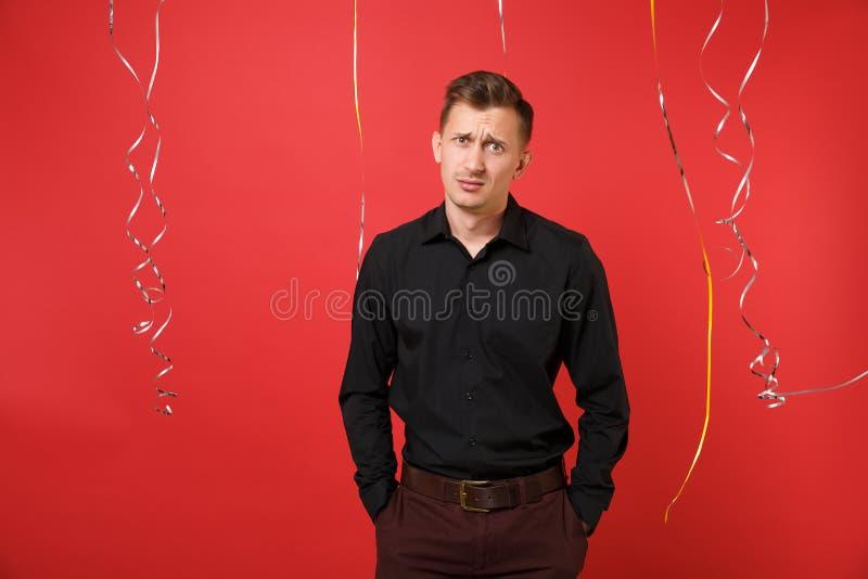 Δυσαρεστημένος μπερδεμένος νεαρός άνδρας στο μαύρο κλασικό εορτασμό πουκάμισων στο φωτεινό κόκκινο υπόβαθρο με serpentine Βαλεντί στοκ φωτογραφία με δικαίωμα ελεύθερης χρήσης