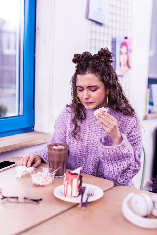 Δυστυχισμένη άρρωστη συνεδρίαση εφήβων μπροστά από το κακάο και το κομμάτι του κέικ στοκ εικόνες με δικαίωμα ελεύθερης χρήσης