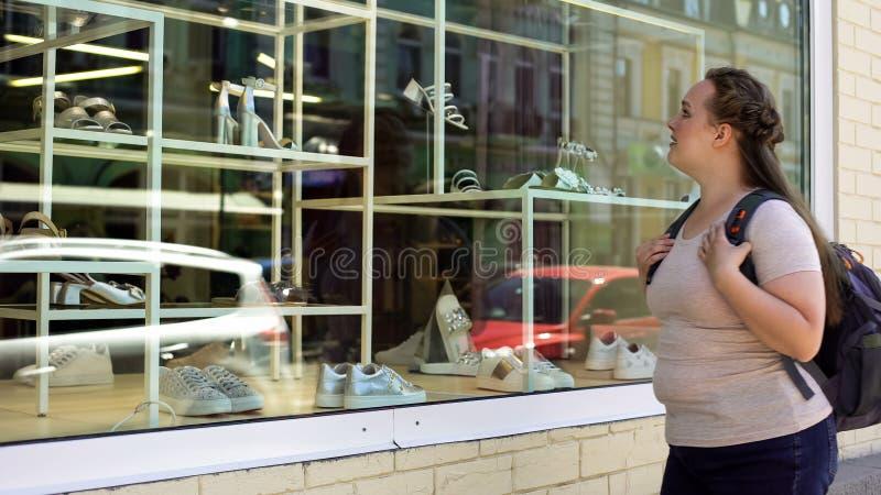 Δυστυχισμένο φτωχό θηλυκό που εξετάζει την προθήκη με τα παπούτσια, ακριβά υποδήματα στοκ εικόνα