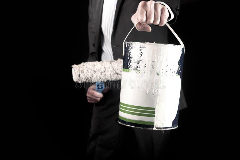 Î'usinessman que sostiene el rodillo de pintura y un cubo de pintura fotografía de archivo libre de regalías