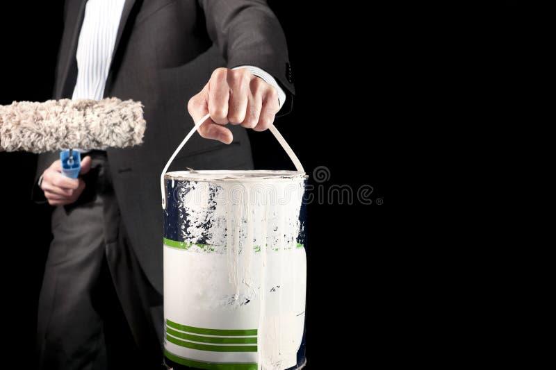 Î'usinessman que sostiene el rodillo de pintura y un cubo de pintura fotos de archivo libres de regalías