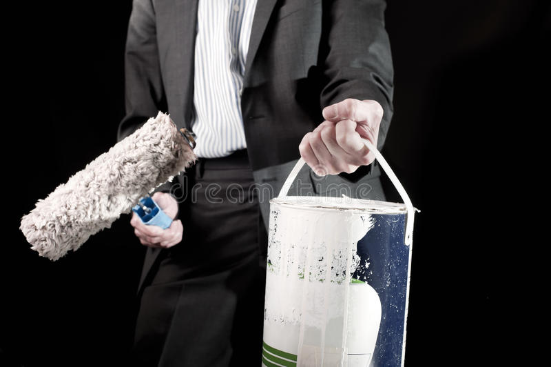 Î'usinessman que sostiene el rodillo de pintura y un cubo de pintura foto de archivo libre de regalías