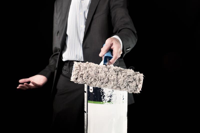 Î'usinessman que sostiene el rodillo de pintura y un cubo de pintura imagen de archivo libre de regalías