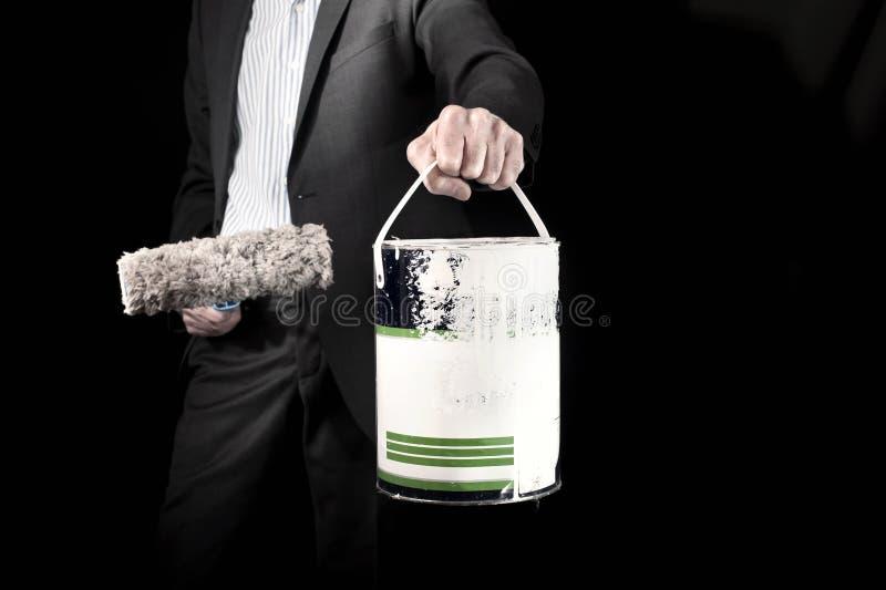 Î'usinessman que sostiene el rodillo de pintura y un cubo de pintura imagen de archivo
