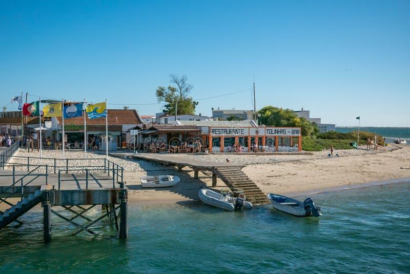 Île d'Armona en Algarve, Portugal. Plage avec jetée en bois, bateaux et restaurant photo libre de droits