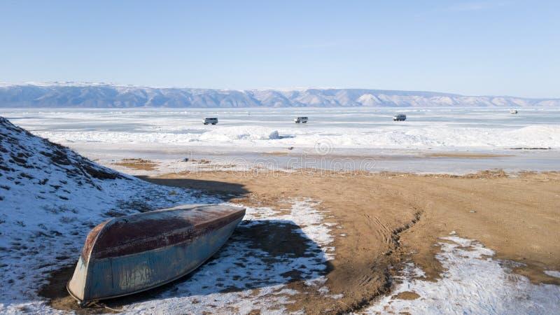 Île d'Olkhon en hiver : sur le rivage est un vieux bateau délabré inversé sur la glace dans la distance mettent trois voitures photo libre de droits