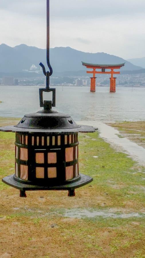 Île de Miyajima, Hiroshima, JAPON - août 10, 2017 : Une lanterne et un grand Torii dans le tombeau d'Itsukushima images stock