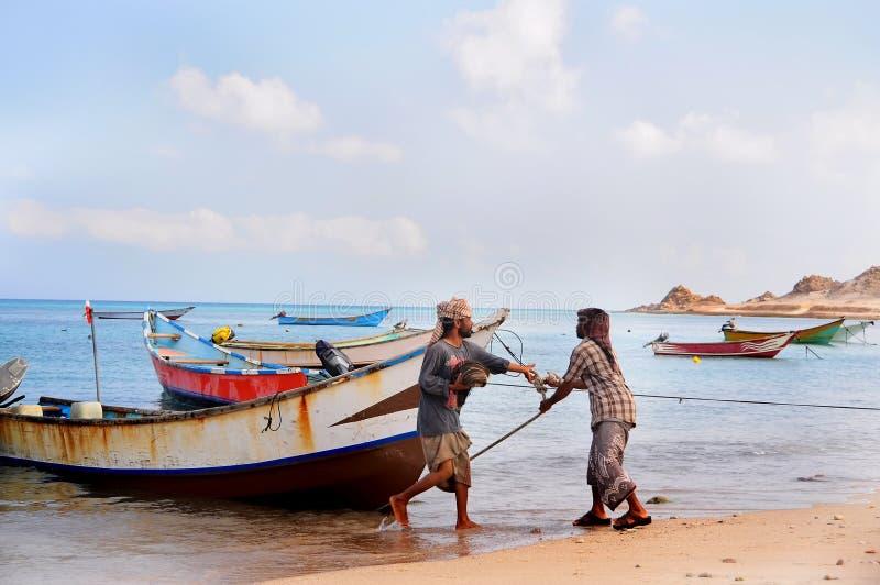 Île de Socotra, Yémen, le 9 mars 2015 pêcheurs ruraux simples retournant de la pêche pour traîner le bateau hors de l'eau sur les images stock