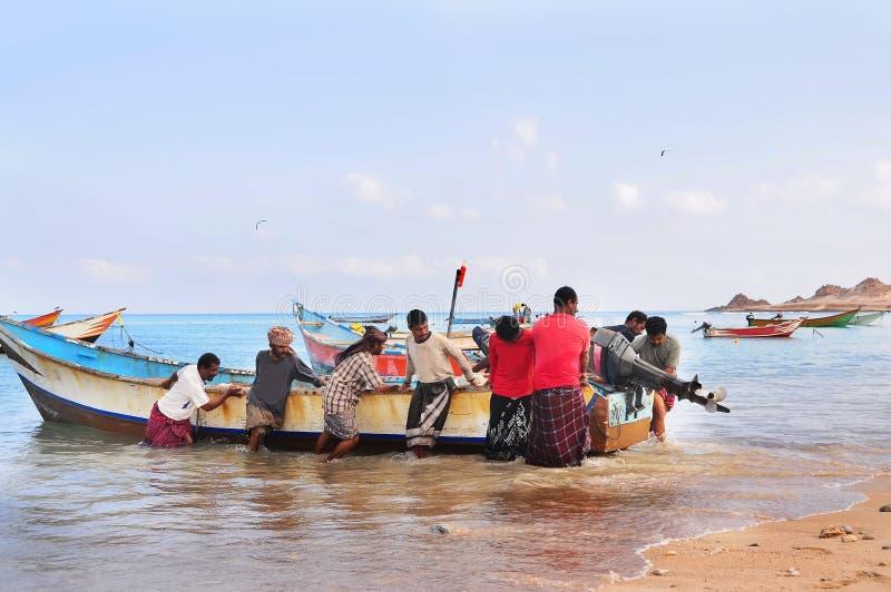 Île de Socotra, Yémen, le 9 mars 2015 pêcheurs ruraux simples retournant de la pêche pour traîner le bateau hors de l'eau sur les photographie stock