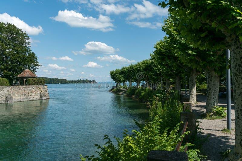 Île et canal avec le chemin couvert d'arbre de bord de lac sur le Lac de Constance photographie stock