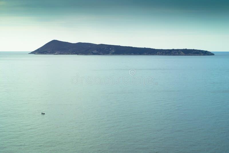 Île et petit bateau de pêche sur la mer calme photographie stock
